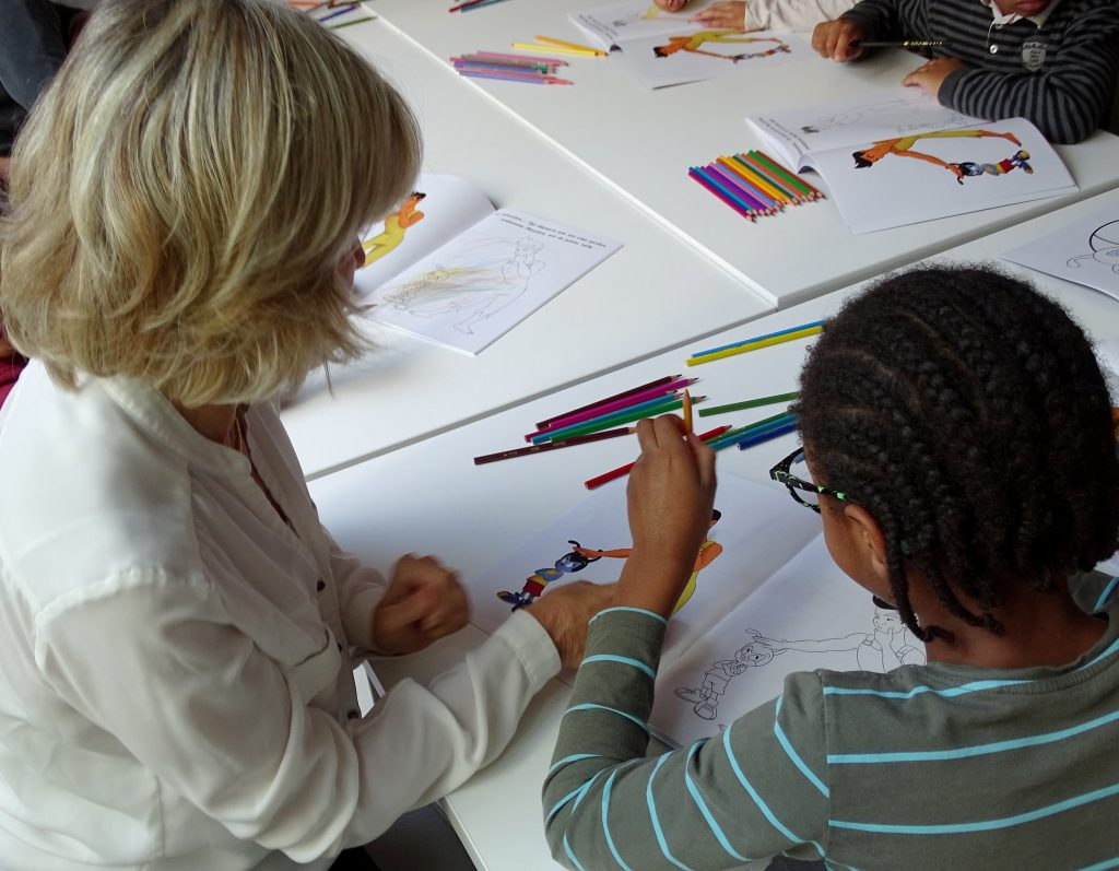 Les enfants en plein coloriage de leur cahier ludo pédagogique accompagnés de Stella