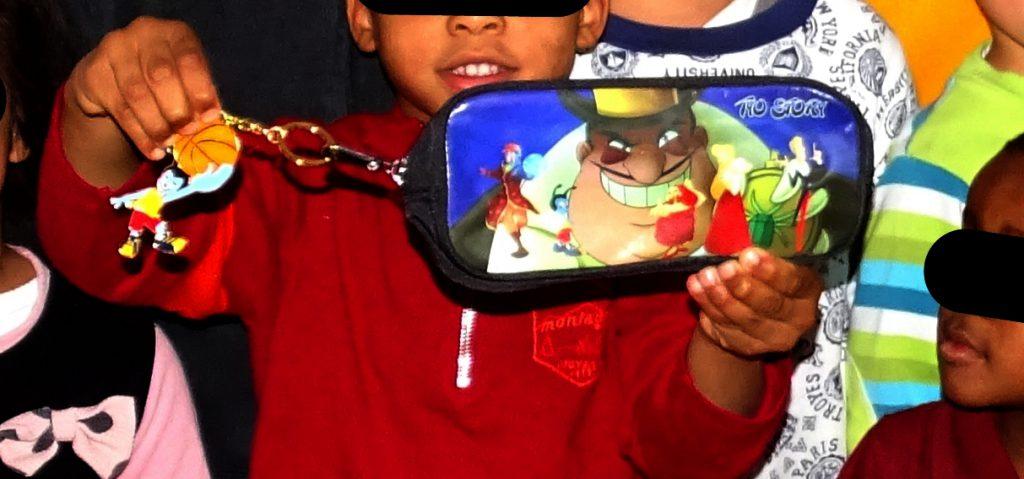 Trousse à l'effigie des personnages de Tyo Story et Porte clef Mouchtic tenus par un jeune garçon